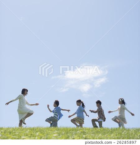 นักเรียนระดับประถมศึกษากำลังเดินไปตามหญ้าและครู 26285897