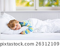 happy little kid boy after sleeping in bed in 26312109