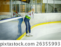 Beautiful girl in winter clothes and skates on ice 26355993