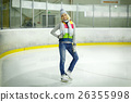 Beautiful girl in winter clothes and skates on ice 26355998