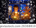 Little kid boy standing by window at Christmas 26368810