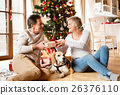 Senior couple in front of Christmas tree with 26376110