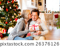 Senior couple in front of Christmas tree with 26376126