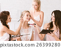 Cheerful bridesmaids helping the bride to get 26399280
