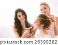 Happy bridesmaids helping the bride to get ready 26399282