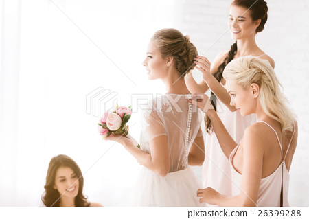 Delighted bridesmaids helping the bride to get 26399288