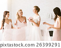 Smiling bridesmaids holding the dress of the bride 26399291
