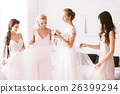 Amused bridesmaids touching the dress of the bride 26399294