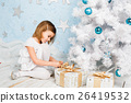 girl unties the ribbon on a Christmas present 26419532