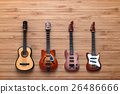 Set of four guitars on a wooden background. 26486666