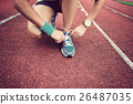 young woman runner tying shoelaces on tracks 26487035