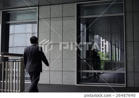 businessman walking toward a glass window 26487640