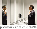 Man getting dressed in a public restroom with mirror 26509496