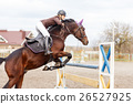 Young rider girl at show jumping. Jump hurdle 26527925