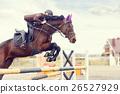 Young rider girl at show jumping. Jump hurdle 26527929