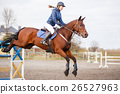 Young rider girl at show jumping. Jump hurdle 26527963