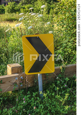 Turn way road sign on roadside in front of green 26541414