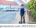 Little kid boy in helmet riding with his scooter 26555023