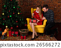 The man gives a gift girl near the Christmas tree 26566272
