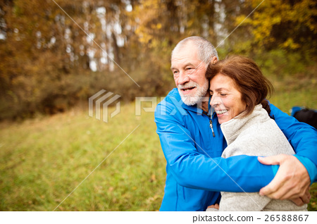 Beautiful senior runners hugging outside in sunny 26588867