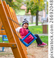 Cute little girl swinging on seesaw on playground 26692048