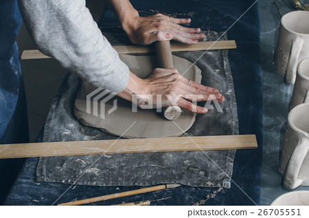 Person using rolling pin to flatten clay 26705551