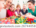 Child on birthday party blowing candles on cake 26744058