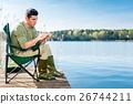 Man fishing at lake fixing lure at angling rod 26744211