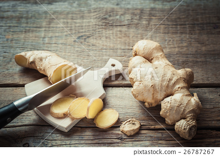 Ginger root on cutting board on kitchen table. 26787267