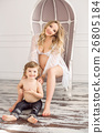 Blonde pregnant woman with her child boy in white 26805184