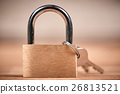 Padlock and keys on a brown wooden table 26813521