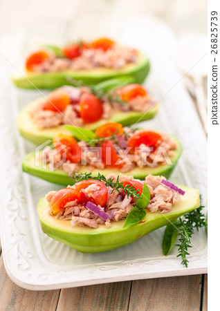 Stuffed avocado on tray. 26825739