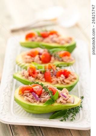 Stuffed avocado on tray. 26825747