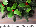 Holly and fir twigs on wood wall 26828050