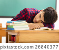 male Student sleeps on the desk in classroom 26840377