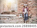 Hipster girl leaning against the old temple wall. 26898405