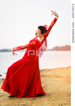 Woman in long red dress stay in dancing pose 26914913