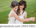 Two beautiful brides dancing on the green field 26915881