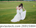 Two beautiful brides embracing on the green field 26915884