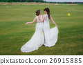 Two beautiful brides embracing on the green field 26915885