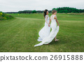 Two beautiful brides walking on the green field 26915888