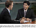 Caucasian man talking to Indian man at table 26956162