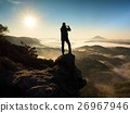 Tourist takes photos with smart phone on hill 26967946
