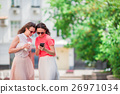 Happy young girl with smartphone walking on 26971034