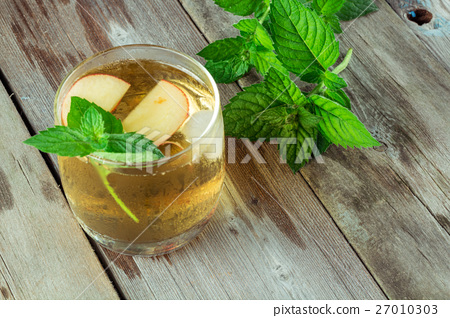 Stock Photo: Glass of cool green tea with mint and apples