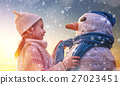 girl playing with a snowman 27023451