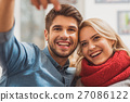 Joyful young man and woman making selfie 27086122