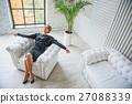Smiling advisor relaxing on armchair 27088339