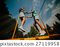 Couple jumping on trampoline in the park 27119958