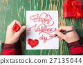 Man writing a Valentines day card  27135644